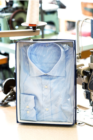 button down shirt: Handmade button down shirt in retail packaging displayed upright in a box in a tailors shop