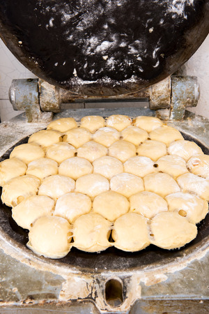 batch: Close up view of raw bread dough in a dough proportioning machine with the lid open and a view of a batch of white rolls Stock Photo