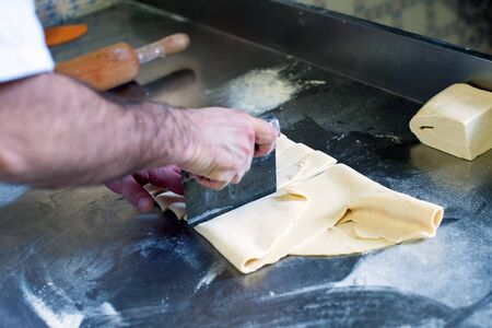forming: Baker forming and shaping dough or rolled pastry with a blade on a metal work table in the bakery, close up of his hands