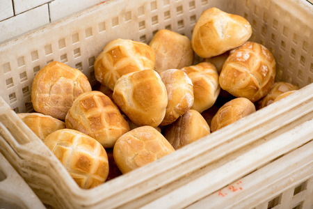crust crusty: Traditional bakery plastic basket filled with freshly baked crusty white bread rolls ready for sale in the shop
