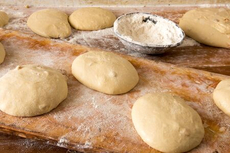 haciendo pan: Portions of dough for making bread left to rise on a wooden table in a bakery, high angle view