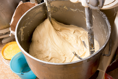 cake mixer: View inside the bowl of an industrial mixer and blender in a bakery with raw dough inside and ingredients round the outside, high angle close up view