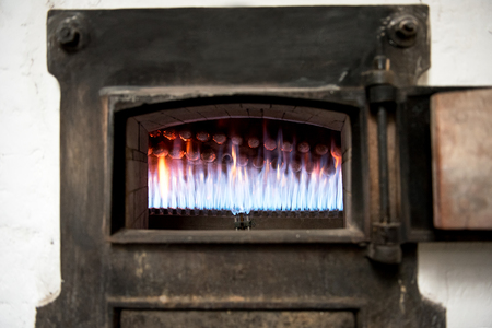 bakery oven: Burning gas jets in an old bakery oven with hot blue flames viewed through the door