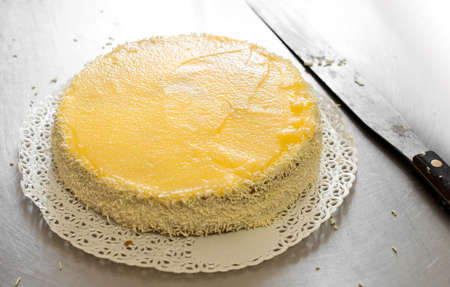 gateau: Preparing a cream cake or gateau in a bakery spreading the layer cake with a topping or filling with a long spatula, close up view