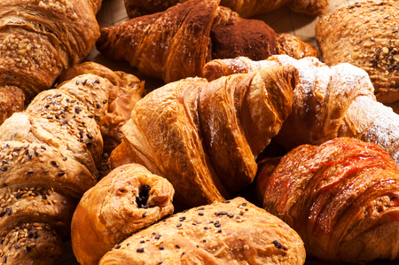 accompaniment: Cropped close up view on pile of various flavored croissant pastries with poppy seeds, sugar and sesame seeds Stock Photo