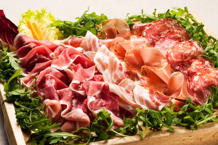 cold: Close up of various salami meat cold cuts in box surrounded with greens on all four side