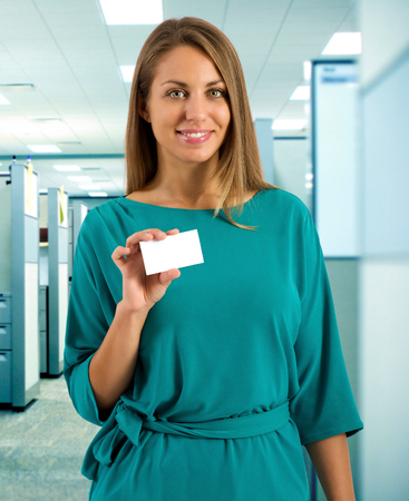 exhibiting: Single cute smiling young adult woman wearing green dress stands among office cubicles while holding up a blank business card with copy space Stock Photo