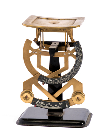 payable: Vintage brass letter scale for weighing letters with a double scale of weights to calculate the postage payable for the mail, isolated on white