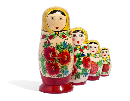 decreasing in size: Row of four matryoshka dolls in front of each other over white background with shadows Stock Photo
