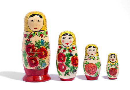 decreasing in size: Row of four Russian matryoshka dolls lined up next to each other over white background with shadows