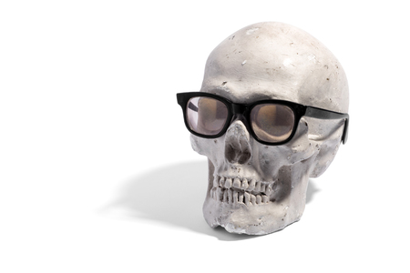 black rimmed: Fun conceptual image of the model of a human skull wearing black rimmed spectacles or eyeglasses over white with copy space