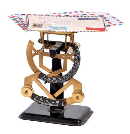 payable: Vintage brass letter scale with a pile of letters on the top plate for weighing to calculate the postage payable on the double numbered scales below, isolated on white Stock Photo