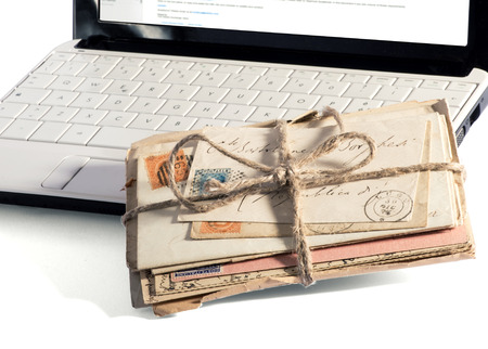 bundle of letters: Bundle of letters tied with string resting on a laptop keyboard in a conceptual image of email correspondence , close up low angle of the envelopes and keyboard Stock Photo