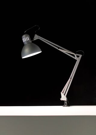 hinged: Single adjustable hinged desk lamp attached to white surface over black background Stock Photo