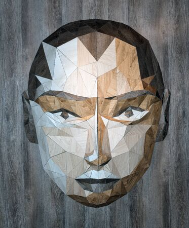 marqueteria: incrustaci�n geom�trica cara de madera decorativa hecha de piezas triangulares de madera de diferentes colores sobre un panel de madera Foto de archivo