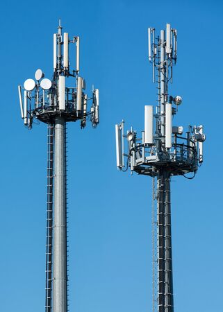 to and fro: Two telecommunications towers with satellite dishes and antennae fro transmitting and receiving broadcasting signals against a sunny blue sky with copy space Stock Photo