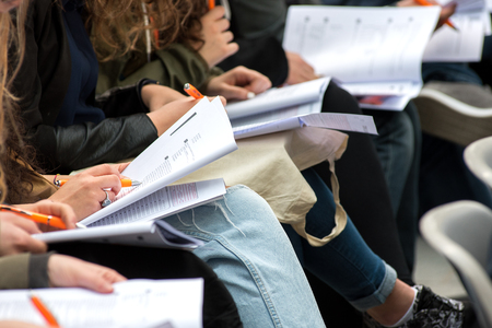 questionnaires: Students sitting in a row on chairs writing a test or exam with their questionnaires and notes balanced on their laps, close up view