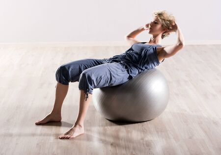 stability: Young barefoot woman doing sit ups with hands behind head on large gray colored stability ball on hardwood floor