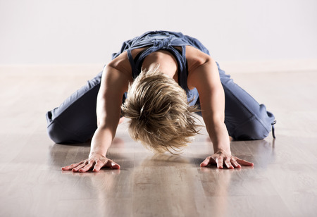 head down: Single young blond woman with head down stretching hip flexor joint muscles on hardwood floor in studio Stock Photo