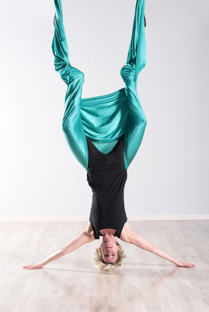 supple: Single upside down woman doing aerial yoga with legs wrapped up in large green flexible tarp suspended from ceiling and head on floor in studio Stock Photo
