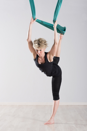 balances: Single blond woman in black outfit stretching legs back with green tarp suspended from ceiling for aerial yoga workout