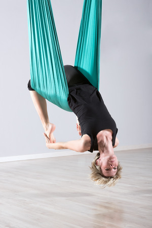 supple: Single upside down woman doing aerial yoga back bends with assistance of large green flexible tarp suspended from ceiling