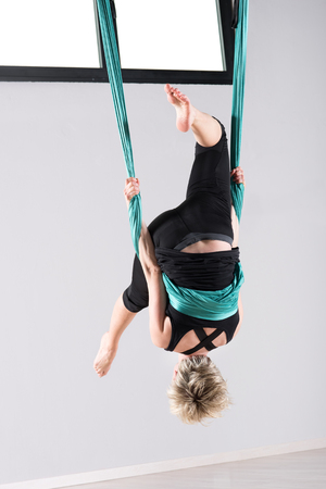 suspended: Upside down woman performing an aerial yoga somersault while suspended from ceiling with green cloth