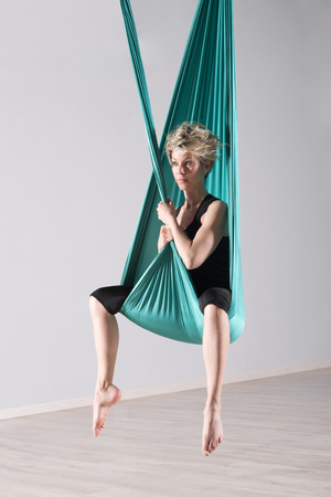 lithe: Single calm woman sitting with toes pointed down while doing intense leg stretching exercises wrapped in aerial yoga blanket suspended from ceiling