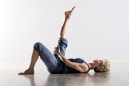 hamstring: Single athletic woman with blond hair in blue outfit on back stretching hamstring muscles for leg in mid air