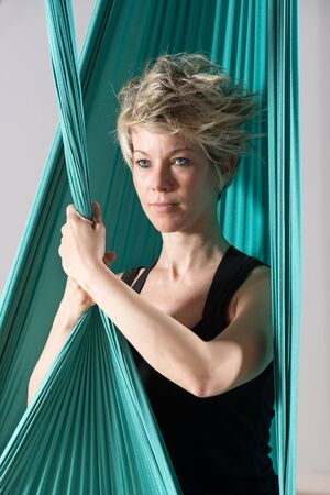 pleated: Close up on confident blond athletic woman holding on to pleated green aerial yoga tarp over gray background Stock Photo