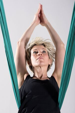 poise: Beautiful woman in prayer pose leaning back in stretching exercise with aerial yoga blanket over gray background Stock Photo