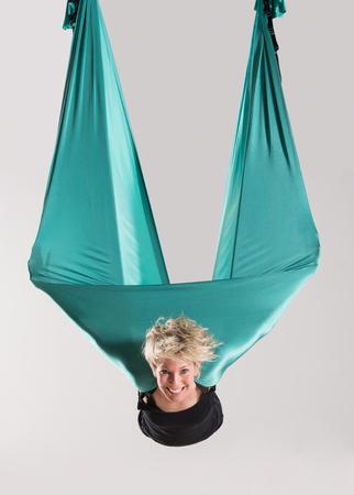 Smiling mid air young blond adult woman doing aerial yoga with arms wrapped in large green flexible tarp suspended from ceiling