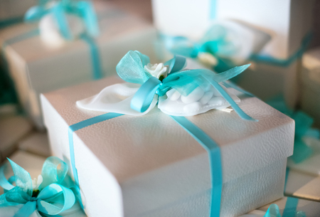 giftwrapped: Decorative gift-wrapped party favor in a box tied with a turquoise blue ribbon and bow for a catered celebration or festive party