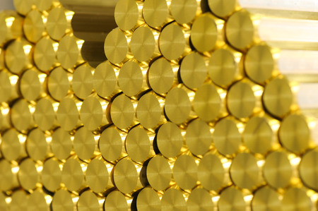 manufactured: Close up on ends of newly manufactured shiny brass rods in a neatly arranged stack for industry concept