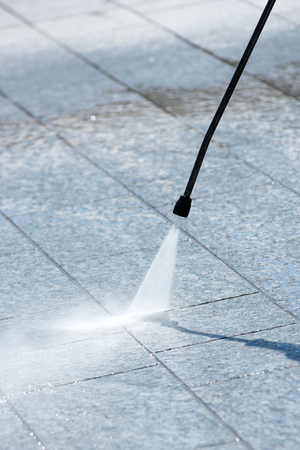 Using a pressure hose to power clean outdoor stone paving with a jet of water from the fine nozzle , no person with selective focus to the equipment