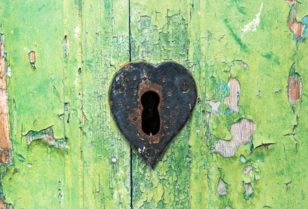 escutcheon: Old grungy green wooden door with peeling paint and rusted lock with a heart shaped escutcheon around the key hole