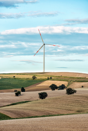 sustainable resources: Rolling agricultural hills with a single wind turbine in the distance on the horizon providing renewable electricity from natural sustainable resources