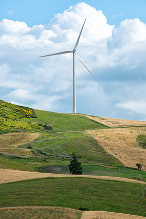 kinetic energy: Single wind turbine providing renewable energy on top of a rural hill with agricultural fields and meadows below against a cloudy blue sky