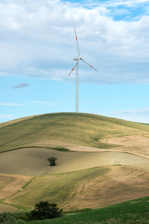kinetic energy: Single wind turbine in farmland on a hilltop with rolling fields and meadows providing a source of renewable electricity from the conversion of the kinetic energy of the wind Stock Photo