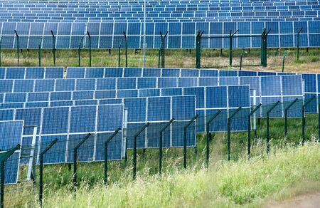 sun energy: Solar energy farm with rows of photovoltaic panels in a grassy field providing a supply of electricity by converting solar energy from the sun Stock Photo