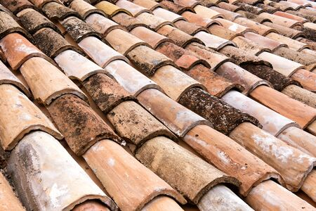 semicircular: Old weathered and discolored clay roofing tiles detail with rows of overlapping semi circular curved tiles on a roof in a full frame view