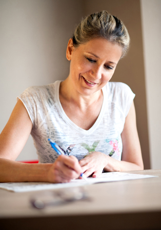 filling out: Single beautiful mature woman with pretty smile and tied back hair writing notes or filling out a form with pen at table indoors Stock Photo
