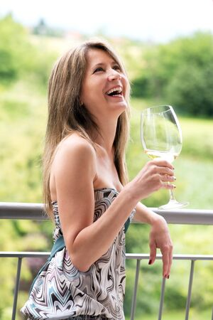 vivacious: Vivacious woman celebrating on an open-air patio drinking a glass of wine or alcohol looking up and laughing