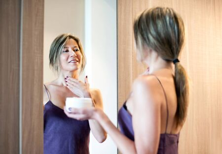 ageing: Cheerful beautiful woman with long hair and purple night gown looking in mirror while applying wrinkle cream Stock Photo