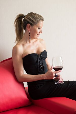 demure: Elegant woman in a black cocktail dress sitting demurely on the arm of a sofa drinking a glass of red wine at a party