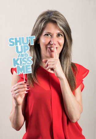 shushing: Half Body Shot of an Attractive Adult Woman in Shushing Gesture, Holding a Photo Booth Prop and Smiling at the Camera. Stock Photo