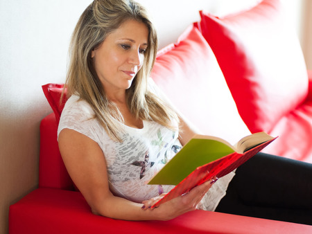 hard cover: Single smiling gorgeous mature woman in white blouse reading a hard cover book while relaxing on red sofa indoors