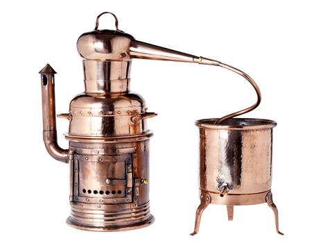 destilacion: alambique de cobre de la vendimia vieja usada para la destilación de líquidos con dos vasos, uno con un quemador, conectados por un tubo aislado más de blanco