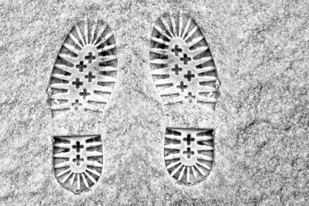 clear away: Clear deep footprints on white winter snow of a pair of boots or heavy soled shoes standing side by side pointing away from the camera, overhead view