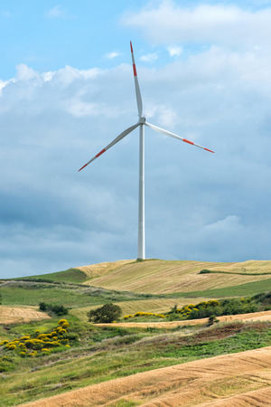 kinetic: Wind turbine on a rural hilltop against a cloudy sky for the conversion of kinetic energy of the wind to electricity in a power and energy concept Stock Photo